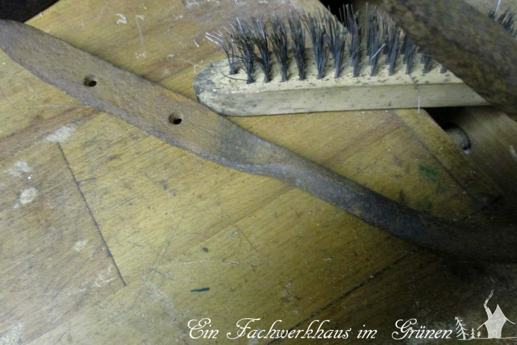 Alter verrosteter rustikaler Wandhaken und eine Drahtbürste.