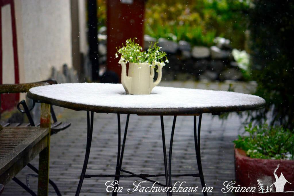 Gartentisch, mit Schnee bedeckt.