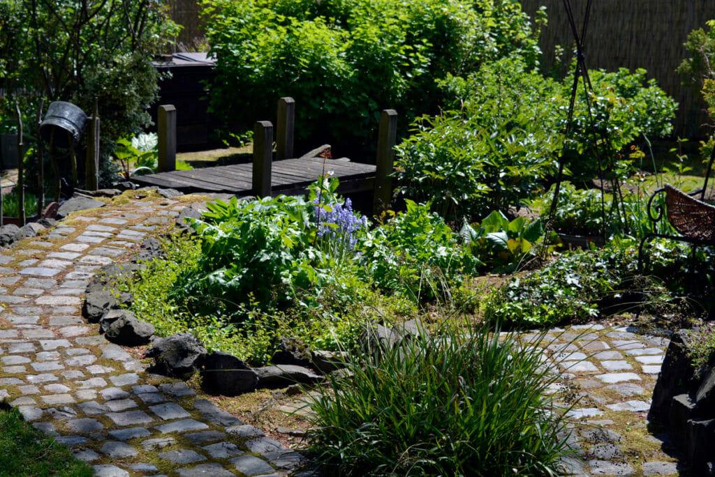 Einen Garten gestalten. Hier führt der Weg zu einer Brücke.